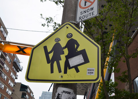 yellow pedestrian crossing sign that has been altered to look like 2 art students, one with a cardboard tube and the other with a portfolio case