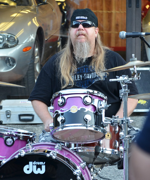 bearded man with sunglasses and black basebell cap sits at a drum set. Hhis baseball cap says Zedhead on it.