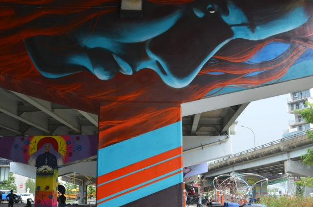 a large blue face mural, horizontal, looking down at the park below