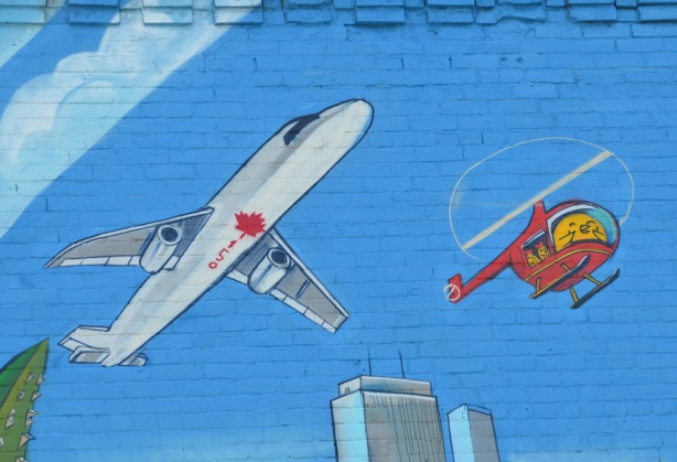 part of a large mural, blue sky painted background, the underside of an airplane as it passes overhead, painted with 150 and a red maple leaf, flying beside it is a red helicopter with a Uber5000 birdie flying it.