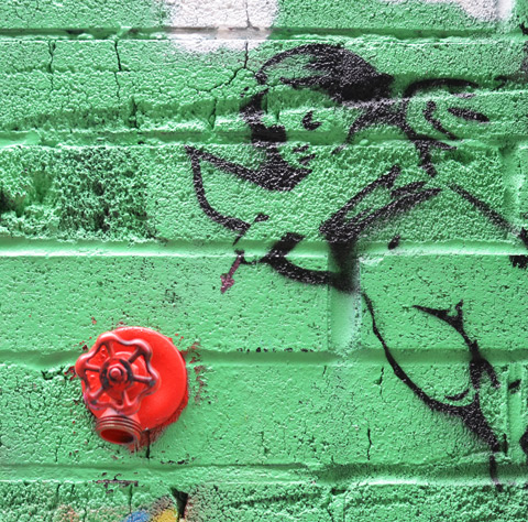 green background to a piece of graffiti that is black line drawing of cupid shooting an arrow. The target is a real tap in the wall that has been painted bright red