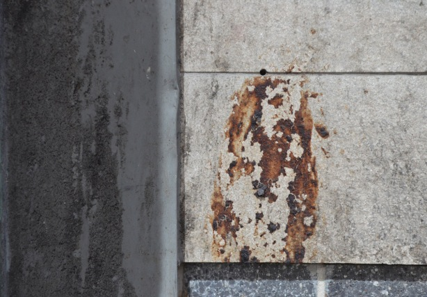 dirt on an exterior wall that looks like the top part of a person