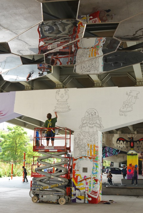 a man is painting a mural on a concrete bent at Underpass park, up on a lift, he is reflected in the mirrors on the ceiling of the park, Al Runt