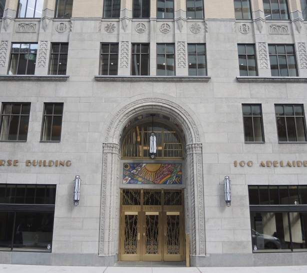 entrance to 100 Adelaide West, a stone building, with brass decorated doors and mosaic pictures decorating it. The concourse building, with stone relief work between the third and fourth storey windows as well