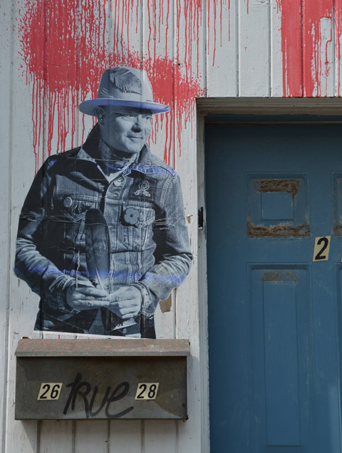 a black and white image of Gord Downie from Barenaked Ladies group, wearing his hat, outside a blue door at number 28