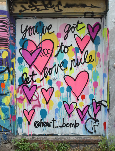 graffiti on a door in an alley, pink and purple hearts with the words, you've got to let love rule, a piece by heart_bomb
