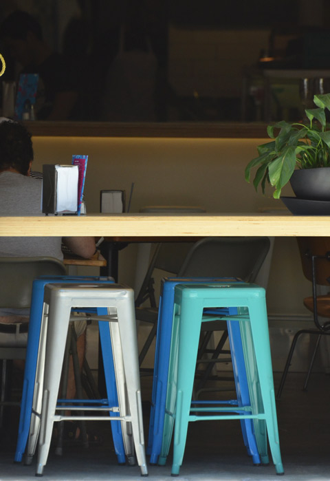 white, teal, and blue metal stools beside a wood table, in the window of a restaurant, in the sun, a man is sitting with his back to the table.
