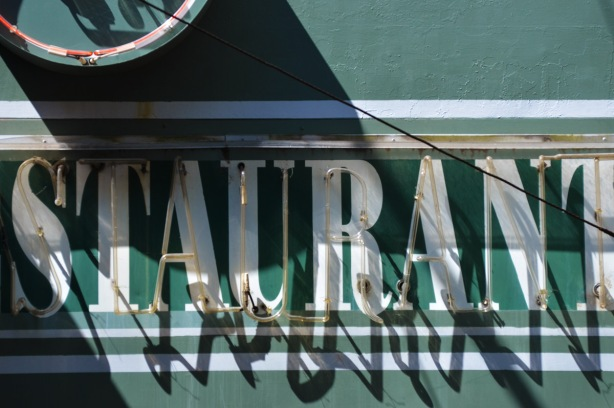 part of a green sign, with white letters that say restaurant.