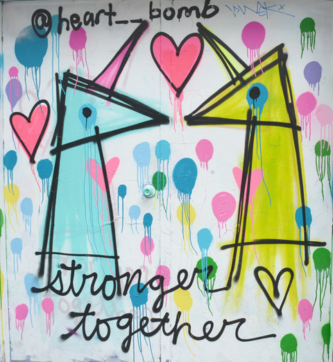 graffiti on a laneway door, two unicorns, one yellow and one blue, looking at each other with a heart above them, words say: stronger together, a piece by heart_bomb