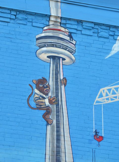 part of a larger mural, a monkey in a sheepskin jacket is climbing the CN tower. A small black figure is sitting on top of the tower.