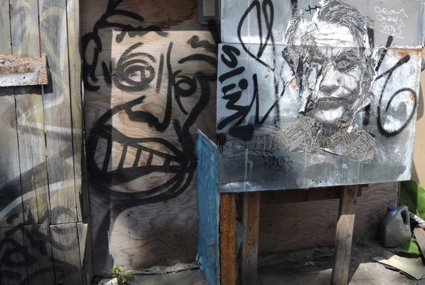 in an alley, two graffiti pieces. One is a pasteup, realistic and detailed drawing of Heath Ledger as the Joker and the other is a quick black line drawing of a man's face