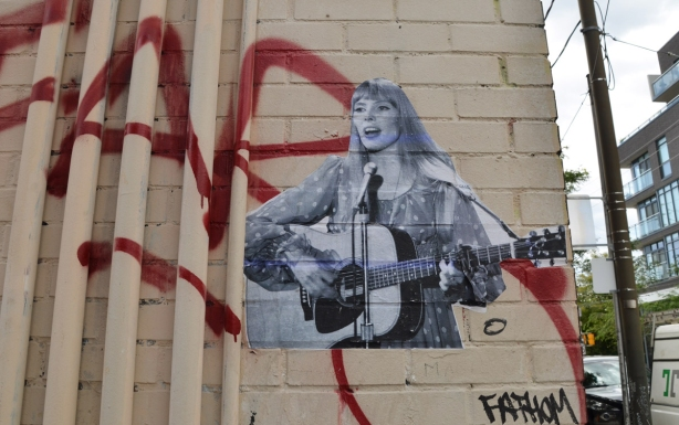 a black and white pasteup of Joni Mitchell playing her guitar and singing