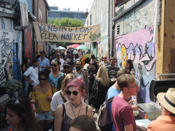 a large number of people in an alley. A banner over the alley says Kensington Flea Market and Beer Garden