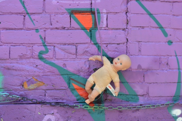 purple wall, graffiti onthe wall, also a chain runs horizontally across the bottom of the picture. A toy doll with no clothes has its arm tucked into a green wire.