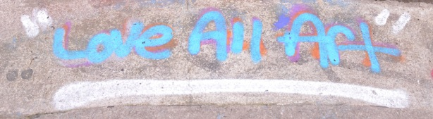 words painted on a sidewalk in blue, love all art