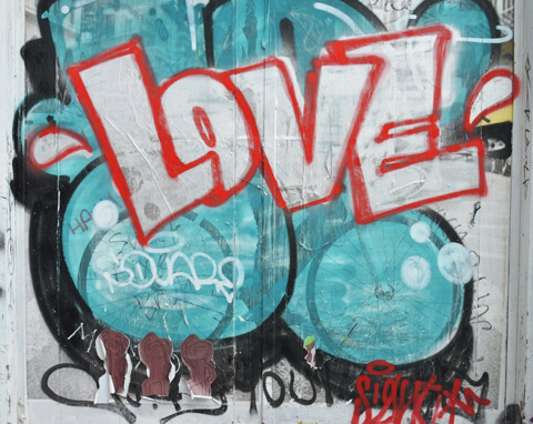 the word love in white block letters that are outlined in red, background is turquoise bubbles. below that are three brown pasteups of monkeys