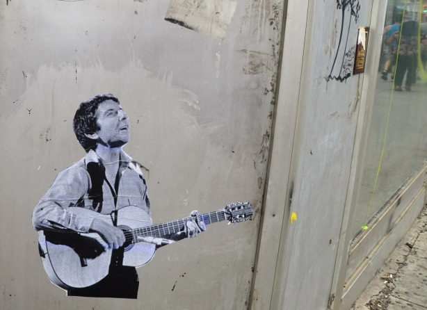 a black and white pasteup of an image of a male guitar player, young man, on a grey wall