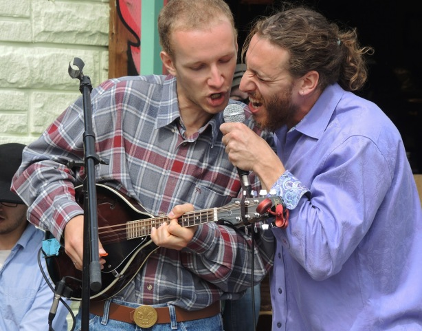 two musicians, one is playing a mandolin and singing the other is just singing, they are both sharing the same microphone
