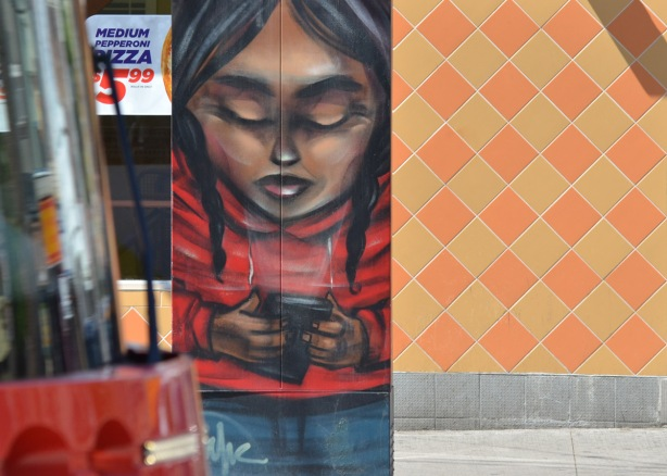 a metal box on the sidewalk is painted by elicser, a young girl in a red shirt and blue jeans, holds a black phone, behind her is the orange diamond tiles of a Pizza Pizza restaurant, the very front of a streetcar is on the left.