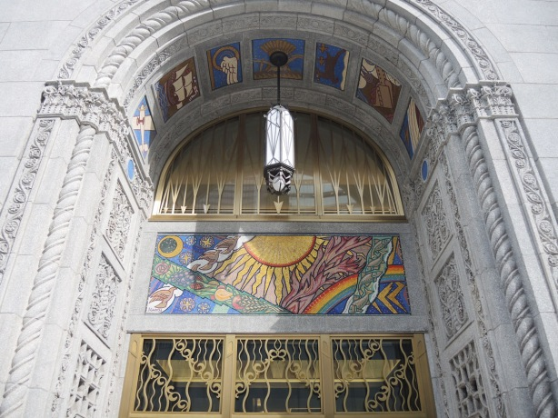 entrance to 100 Adelaide West, a stone building, with brass decorated doors and mosaic pictures decorating it.