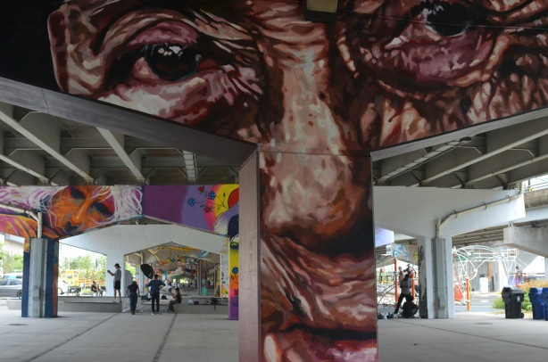 urban open space under a bent that has been painted with a wrinkly brown man's face