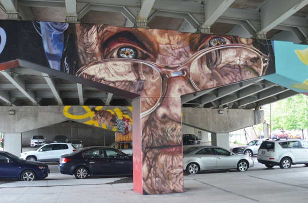 cars parked under a bent that has been painted with a wrinkly brown man's face wearing glasses