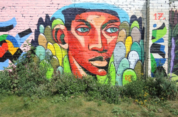 orange face, blue eyes, short black hair, mural on a wall at Sonya Parkette in Kensington