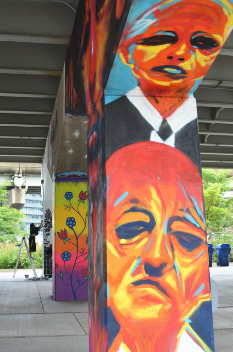 conrete pillar in Underpass park that has been painted with large orangish toned faces, by Carlos Delgado