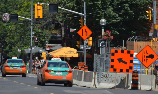 street scene, two orange and green taxis drive by a construction site with orange traffic signs, arrows saying the right lane is closed.