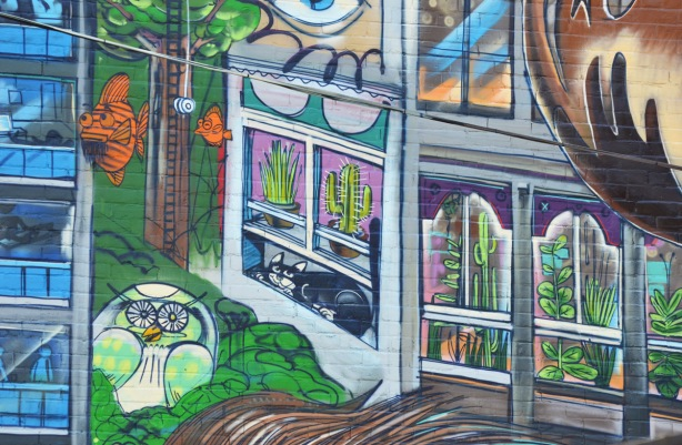 part of Uber 5000 Toronto mural in Graffiti Alley, houses, cat, orange fish, apartments, owl in a tree,