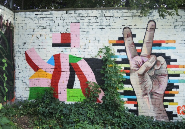 a mural with two parts, on the left is an abstract design with rectangles and a few curves. on the right is a realistic hand giving the peace sign