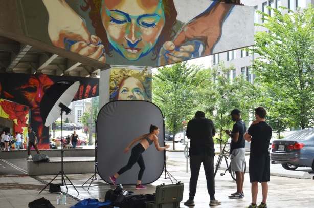 a photo shoot in underpass park, grey screen in front of a mural covered bent, a woman in workout clothes, men behind the camera