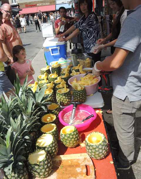 a young man drills out the center of a pineapple while two women blend the chunks into juice. The juice is then poured back into the hollowed out pineapples and sold as a drink