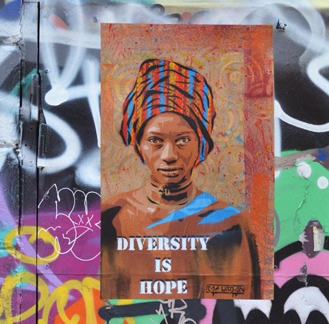 poster street art of a black woman's head and shoulders. She is wearing a head scarf that is striped fabric wound round her head. The words on the poster say Diversity is Hope