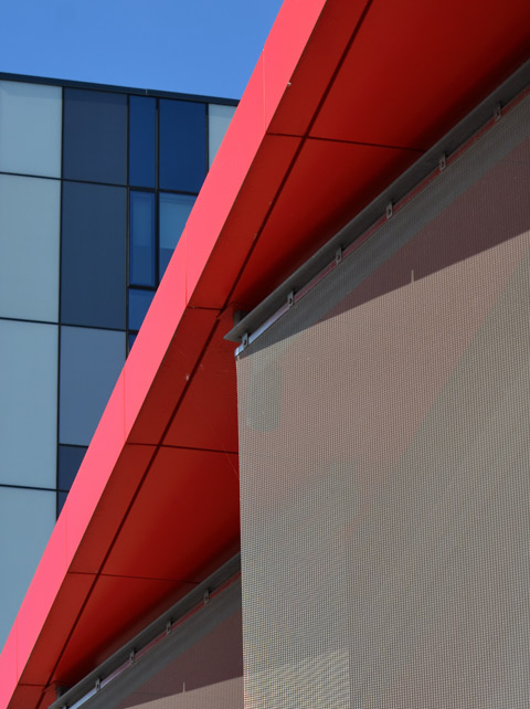 abstract composed of a red roof, a grey textured wall and a building with three tones of blue windows