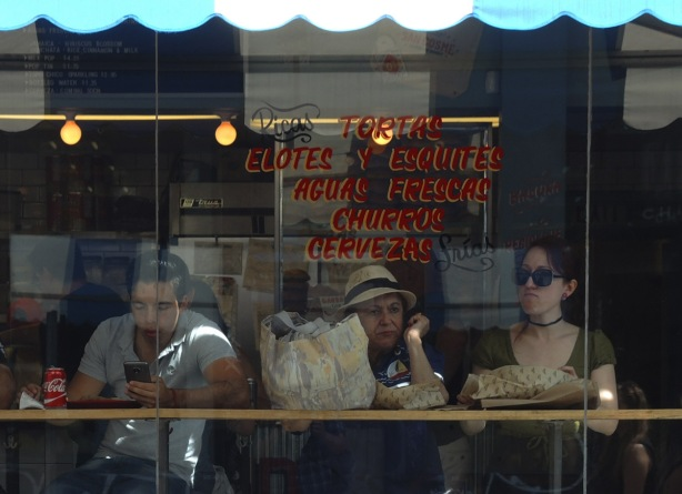 looking into the window of a bakery/restaurant. Three people are sitting at a table that looks out the window. One is one his phone and the other two are looking out the window. The sign on window, in red lettering is Ricas tortas,