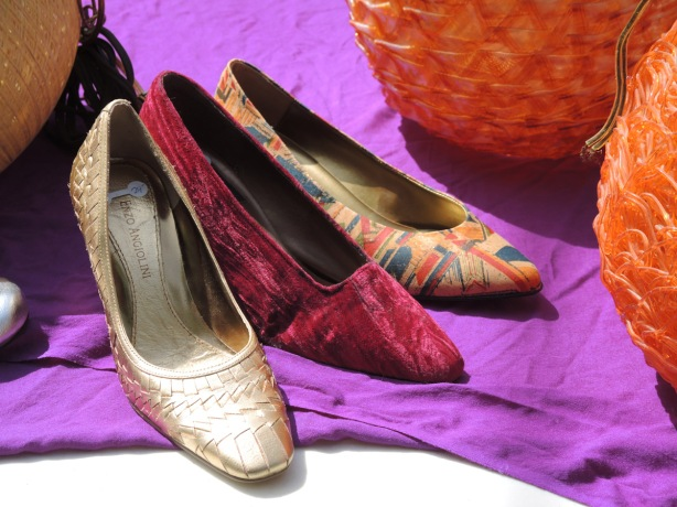 items for sale on a table outside, three shoes (no pairs), one gold, one red velvet and one patterned, on a purple table cloth. Also for sale, two round orange lamp shades