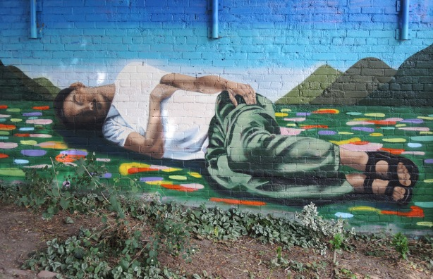 a man in green pants and white t-shirt is sleeping on the ground, a mural on a wall. the ground is green with small circles and semi-circles in other colours.