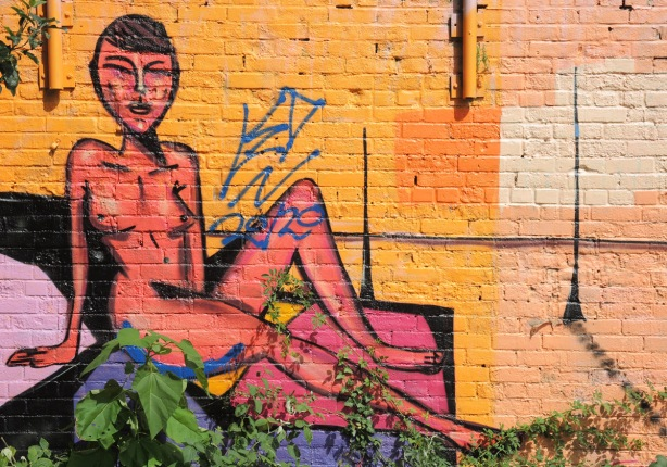 mural of an orange naked woman reclining, wall is golden yellow colour