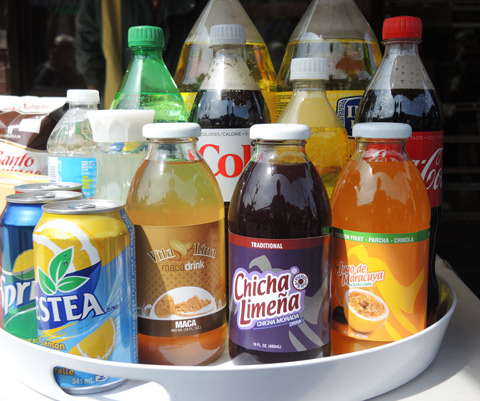 sample of drinks for sale at a food stall at a street festival, nestea, coke, water, some soft drinks as well as south american products like chicha (purple) and