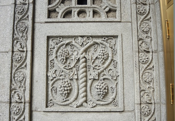 a square panel of stone carved with grapes and grape vines