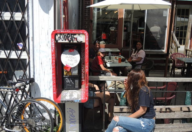 a small phone booth outside a coffee shop with a patio. Some people are sitting on the patio, Moonbean coffee. On the phone is a round white hand written sign that says Please stop busting our phone
