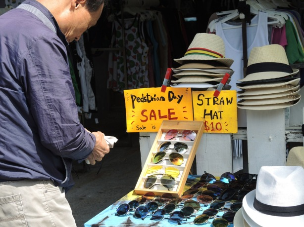 a man looks at sunglasses at a table outside where they are for sale. The sign says Pedstrian Day Sale, sunglasses ten dollars, straw hats ten dollars