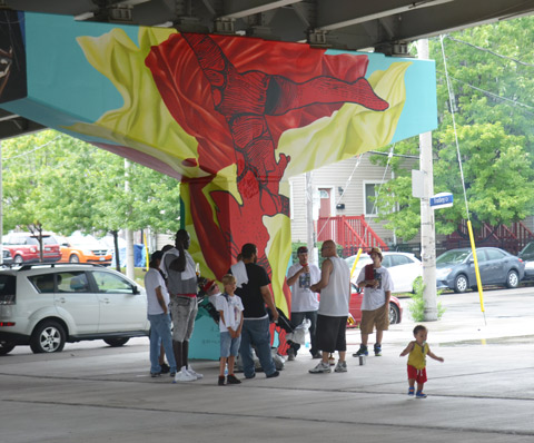 a group of people is having a small party in Underpass park, standing around a concrete bent that has recently been painted with a mural by Annie Hamel