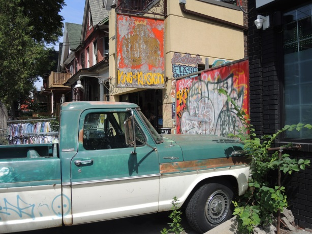 an old green and white pickup truck parked in a driveway in Kensington Market, beside a store with a very faded sign that barely says King of Kensington