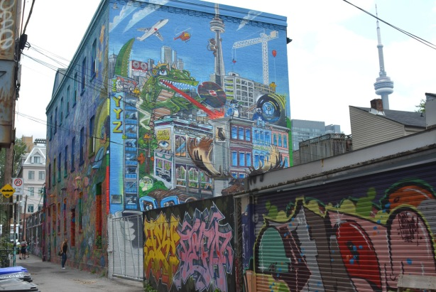 Graffiti alley, large building covered on both sides with murals by Uber 5000, marine life facing the alley and a new Toronto themed mural on the west side, partially obscured by garages in the alley, and behind a chainlink fence.