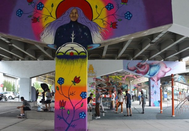 people at Underpass Park, under the expressway, with pillars painted in murals, guys on skateboards,