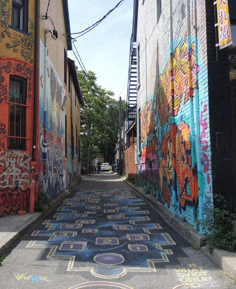 an alley in Kensington with a painting by #whatsvictorupto on the ground - numbers
