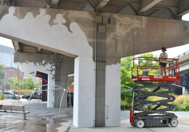 a person stands on an elevated platform and looks at the white outline that they have made in preparation for painting the bent white, the beginnings of a mural
