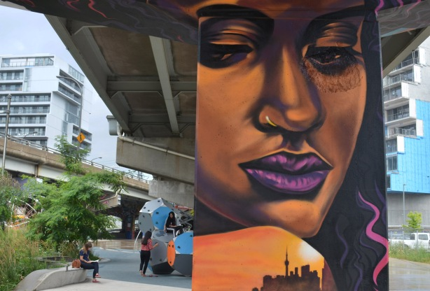 a mural of a woman's face in orange and purple tones, large, purple lips, on a concrete pillar, with young woman sitting in the park in the background